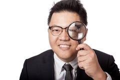 Asiatischer Geschäftsmannblick durch Lupe und Lächeln Lizenzfreies Stockfoto