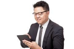 Asiatischer Geschäftsmanngebrauch eine Tablette und ein Lächeln Lizenzfreie Stockfotografie