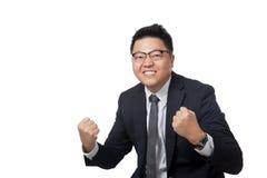 Asiatischer Geschäftsmanngriff seine Fäuste glücklich mit Erfolg stockbild