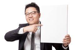 Asiatischer Geschäftsmannpunkt zu einem vertikalen leeren Zeichen und zu einem Lächeln Lizenzfreie Stockfotografie