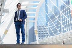 Asiatischer Geschäftsmannstand und denken für das Geschäft, das in der Zukunft erfolgreich ist Konzept des Siegers und des Wettbe stockfotografie