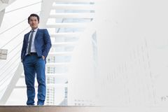 Asiatischer Geschäftsmannstand und -lächeln er denkt für das Geschäft, das in der Zukunft erfolgreich ist lizenzfreie stockfotos