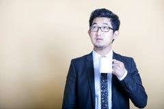 Asiatischer Geschäftsmanntrinkbecher Kaffee stockbild
