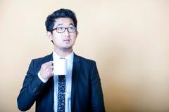 Asiatischer Geschäftsmanntrinkbecher Kaffee lizenzfreie stockfotografie