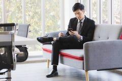 Asiatischer Gesch?ftsmann, der Mobiltelefon im B?ro verwendet lizenzfreie stockfotos