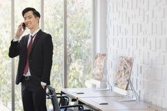 Asiatischer Gesch?ftsmann, der Mobiltelefon im B?ro verwendet lizenzfreie stockbilder