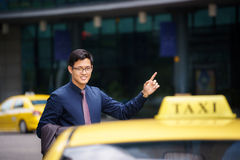 Asiatischer Geschäftsmann, der das Taxiauto verlässt Arbeit nennt Stockfoto