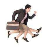Asiatischer Geschäftsmann, der in der Hand mit einem Aktenkoffer, an lokalisiert läuft Stockbild
