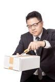 Asiatischer Geschäftsmann, der einen Kasten mit einem Schneidermesser öffnet Lizenzfreie Stockfotos