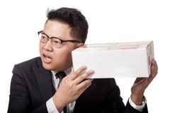 Asiatischer Geschäftsmann ist neugierig, was innerhalb eines Kastens Stockbild