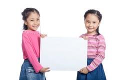 Asiatischer glücklicher Griff der Zwillingsschwestern sehr ein leeres Zeichen Lizenzfreie Stockfotografie