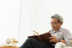 Asiatischer Glasprofessor des alten Mannes, der auf dem Stuhlleselehrbuch sitzt Stockbilder