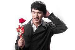 Asiatischer Griff des gutaussehenden Mannes die rote Rose mit Liebe Lizenzfreies Stockbild