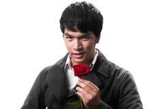 Asiatischer Griff des gutaussehenden Mannes die rote Rose mit Liebe Stockfotografie