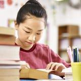 Asiatischer Grundschuleschüler, der ein Buch im Klassenzimmer liest Stockfotografie