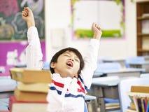 Asiatischer Grundschulestudent, der in Klassenzimmer ausdehnt Lizenzfreie Stockfotografie