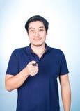 Asiatischer gutaussehender Mann mit den Schlüsseln seines Neuwagens, auf blauem backgro Lizenzfreie Stockfotografie