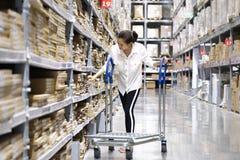 Asiatischer h?bscher Kunde, der Produkte im Speicherlager sucht Das M?dchen, das ihren Handpunkt zum Aufkleber verwendet, um die  lizenzfreie stockfotos