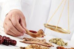 Asiatischer Herbalist, der chinesische medizinische Kräuter wiegt Stockfoto