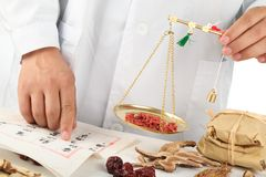 Asiatischer Herbalist, der chinesische medizinische Kräuter wiegt Stockfotografie