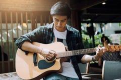 Asiatischer Hippie-Mann ließ Handfangakkord und Spielenmusik lizenzfreie stockbilder