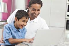 Asiatischer indischer Vater u. Sohn, der Laptop-Computer verwendet Stockfotos