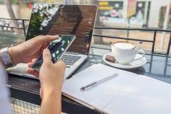 Asiatischer Investor, der die Änderung der Börse auf Laptop und Smartphone aufpasst stockfotos