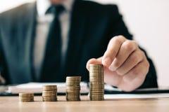Asiatischer Investormann legen Münzen in eine wachsende Position mit Einsparungensfinanzgeldkonzept stockfotos