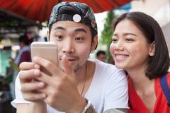 Asiatischer jüngerer Mann und Frau, die auf intelligenten Telefongebrauch für peop aufpasst Lizenzfreie Stockfotos