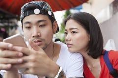 Asiatischer jüngerer Mann und Frau, die auf intelligenten Telefongebrauch für peop aufpasst Lizenzfreies Stockfoto