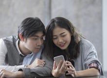 Asiatischer jüngerer Mann und Frau, die am intelligenten Telefon mit glücklichem f aufpasst Stockbilder
