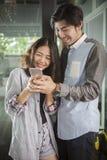 Asiatischer jüngerer Mann und Frau, die am intelligenten Telefon mit glücklichem f aufpasst Stockfoto