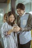 Asiatischer jüngerer Mann und Frau, die am intelligenten Telefon mit glücklichem f aufpasst Stockfotografie