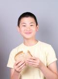 Asiatischer jugendlich Junge, der ein Sandwich isst Lizenzfreies Stockfoto