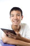 Asiatischer Jugendlicher, der seine Tablette mit Lächeln verwendet Stockfotos