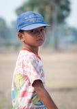Asiatischer Junge, der auf dem Feld des ungeschälten Reises steht Lizenzfreie Stockbilder