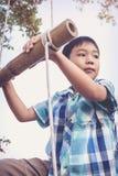 Asiatischer Junge, der auf dem Strickleiter gemacht vom Holz klettert Reise und Einführung Lizenzfreie Stockbilder