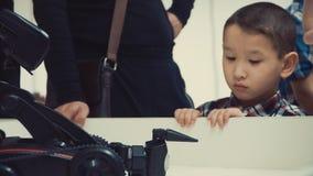 Asiatischer Junge, der auf dem Tisch den Roboter an der Ausstellung aufpasst stock footage