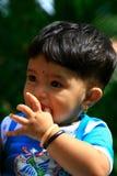 Asiatischer Junge, der Daumen saugt Stockfotografie
