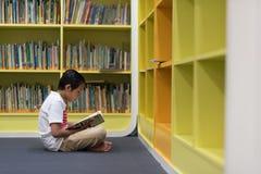 Asiatischer Junge, der ein Buch in einer Bibliothek liest Lizenzfreie Stockfotos