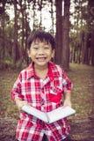 Asiatischer Junge, der ein Buch lächelt und hält getrennte alte Bücher weinlese Lizenzfreie Stockfotos