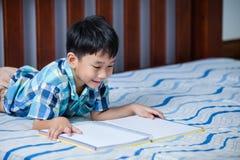 Asiatischer Junge, der ein Buch liest getrennte alte Bücher Stockbilder