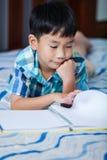 Asiatischer Junge, der ein Buch liest getrennte alte Bücher Stockfoto