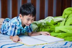 Asiatischer Junge, der ein Buch liest getrennte alte Bücher Lizenzfreies Stockbild