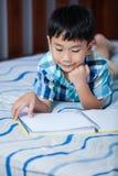 Asiatischer Junge, der ein Buch liest getrennte alte Bücher Stockfotos