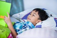 Asiatischer Junge, der ein Buch liest getrennte alte Bücher Lizenzfreie Stockbilder