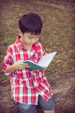 Asiatischer Junge, der ein Buch liest getrennte alte Bücher Abbildung der roten Lilie Stockbilder