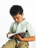 Asiatischer Junge, der eine Zeitschrift liest Stockfotografie