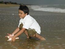 Asiatischer Junge, der im Meerwasser spielt Lizenzfreie Stockfotografie