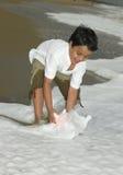 Asiatischer Junge, der im Strand spielt Stockbild